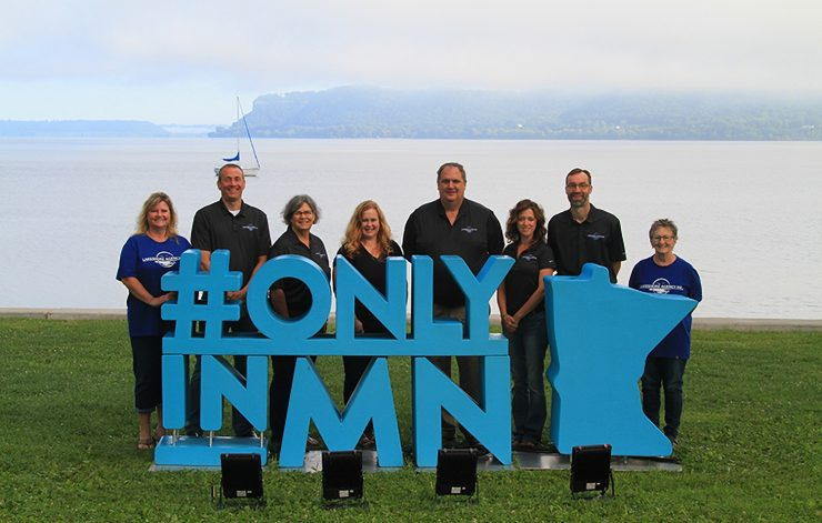 lakeshore agency team photo by lake pepin with #onlyinMN sign